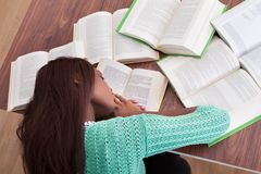 Female student sleeping with books at classroom desk Stock Images
