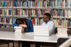 Female Student Sleeping In Library. Sleeping Student Sitting And Leaning On Pile Of Books In College - Shallow Depth Of Field Royalty Free Stock Image