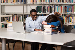 Female Student Sleeping In Library. Sleeping Student Sitting And Leaning On Pile Of Books In College - Shallow Depth Of Field Stock Photo