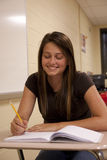 Female student smiling at her desk. Female Student concentrating on her school work at her desk Royalty Free Stock Photo