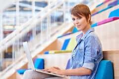 Female student smiling with her laptop in bright public space. Portrait of a pretty young female student smiling gently at the camera while sitting in a brightly Royalty Free Stock Photos