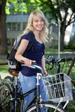 Female student standing with her bike Royalty Free Stock Photography