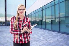 Female student standing on street against modern university buil Stock Photo