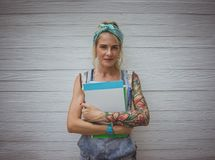 Female student is standing by the white wall with notebooks in his hands in anticipation of classes. Modern girl. Model. Of tattoos royalty free stock photos