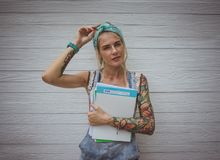 Female student is standing by the white wall with notebooks in his hands in anticipation of classes. Modern girl. Model. Of tattoos royalty free stock images