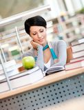Female student studies sitting at the desk Royalty Free Stock Image