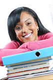 Female student studying. Smiling young black female student with textbooks at desk Royalty Free Stock Photos