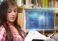 Female Student studying with book and science education interface graphics overlay Royalty Free Stock Photography