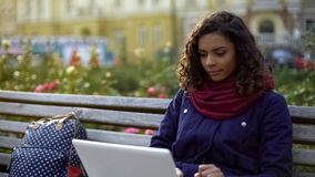 Female student studying on laptop outdoors, writing essay, blogging for website