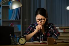 Female student studying for next day exam. Young woman doing homework at night. Tired hispanic girl and college education. Female student studying for next day Royalty Free Stock Photos