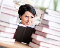 Female student is surrounded with books Stock Photography