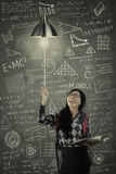 Female student switch on a light bulb Stock Photos