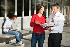 Female Student And Teacher Discussing Over Book On. Happy female student and teacher discussing over book on college campus stock photos