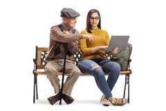 Female student teaching a senior man with a laptop on a bench. Female student teaching a senior men with a laptop on a bench isolated on white background stock photos