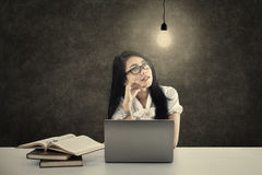 Female student thinking under a lit bulb Royalty Free Stock Image