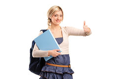 Female student with thumb up. A female student with a school bag holding a book and giving thumb up isolated on white background Stock Images