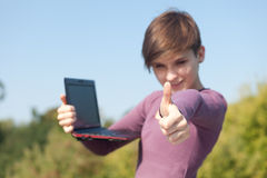 Female student with thumb up using laptop Royalty Free Stock Photo