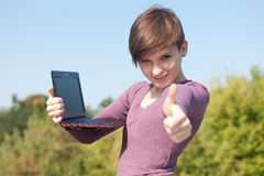Female student with thumb up using laptop Royalty Free Stock Photography