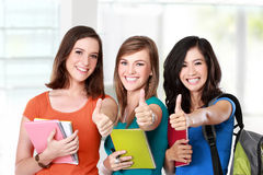 Female student together showing thumbs up. Portrait of a three young female student together showing thumbs up Royalty Free Stock Photography