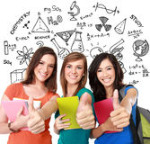 Female student together showing thumbs up. Portrait of a three young female student together showing thumbs up Stock Photo
