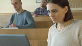 Female student types on laptop. Attractive female student typing on laptop at the lecture hall. Pretty caucasian girl looking at lecturer. Camera pedding from Royalty Free Stock Images