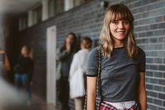 Female student in university campus. Portrait of beautiful young woman walking in college corridor with students standing in background. Female student in Stock Images