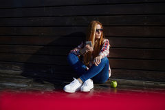 Female student using cell telephone while resting on campus after lectures Royalty Free Stock Photos