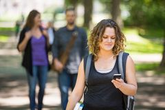Female Student Using Cellphone On Campus. Mid adult female student with backpack using cellphone while standing on campus Stock Images