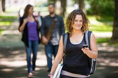 Female Student Using Cellphone On Campus. Portrait of female student with backpack holding cellphone while standing on campus Royalty Free Stock Photography