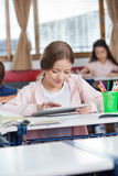 Female Student Using Digital Tablet At Desk. Little female student using digital tablet with friends in background at classroom Royalty Free Stock Images
