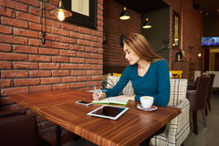 Female student using laptop computer. Young attractive lady keyboarding something on portable net-book while sitting in coffee shop during work break, beautiful Royalty Free Stock Photo