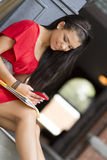 Female student using mobile phone to text. A pretty female student sitting on steps using a mobilel phone outdoors Royalty Free Stock Photos