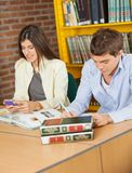 Female Student Using Mobilephone While Friend. Young female student using mobilephone while friend studying in university library Royalty Free Stock Photography
