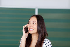 Female student using smartphone in classroom Royalty Free Stock Images