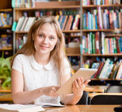 Female student using a tablet computer in a library Royalty Free Stock Photo