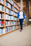 Female student walking in the library Stock Image