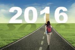 Female student walking toward numbers 2016 Royalty Free Stock Image
