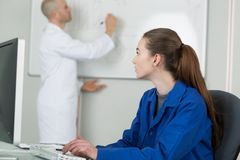 Female student watching educator write on whiteboard. Teacher Royalty Free Stock Image