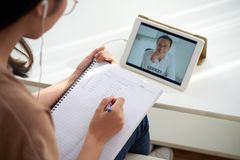 Studying online. Female student watching online lesson and taking notes in textbook royalty free stock photos