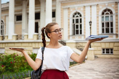 Female student wearing glasses holding tablet and notebooks in different hands outdoors. Stock Photo