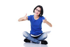 Female student with workbook on knees showing OK. Royalty Free Stock Image