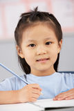 Female Student Working At Desk In Chinese School Royalty Free Stock Photos