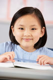 Female Student Working At Desk In School Royalty Free Stock Photography