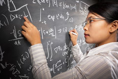 Female student working on equation Stock Images
