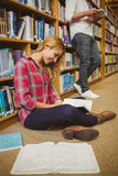 Female student working on floor Royalty Free Stock Photos