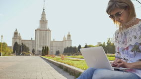 Female student working with a laptop on a square on the background of Lomonosov Moscow State University. stock video