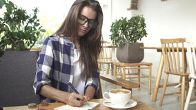 Female student working writing notes in local study hangout cafe. Royalty Free Stock Photo