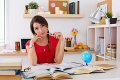 Female student at workplace with pile of textbooks Stock Photo