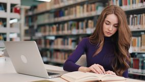Female student works with books and a laptop sitting at the table in the library.  stock video
