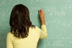 Female student writing on blackboard Stock Photo